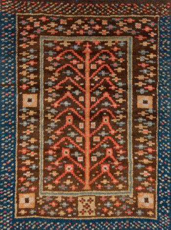 Uma tapeçaria mostra uma árvore estilizada feita de linhas simples, rodeada por uma moldura com vários padrões repetidos.