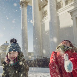 Two children are throwing snow into the air in front of the buildings of downtown Helsinki.