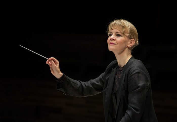 A woman with a conductor's baton is leading an orchestra that is not shown in the photo.