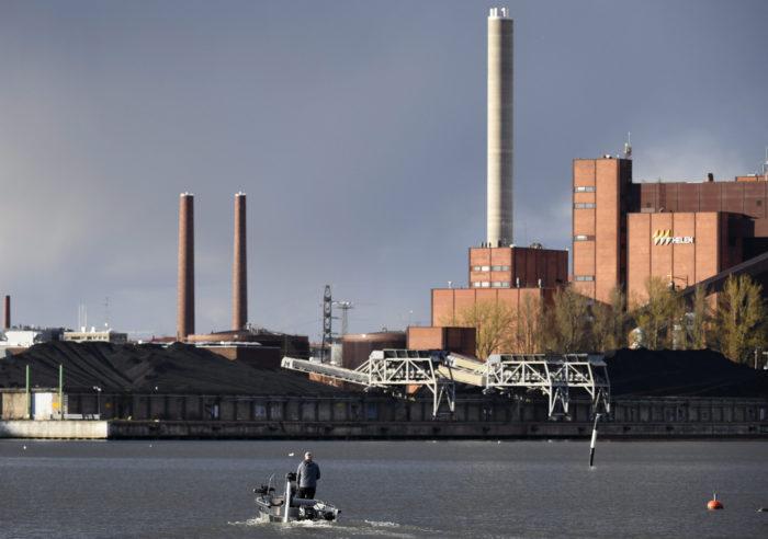 Un barco pequeño pasa junto a una central eléctrica con varias chimeneas.