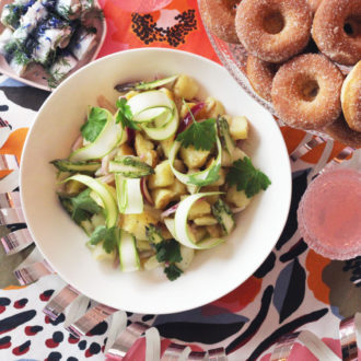 A table is set with glasses of a pink beverage and bowls full of fish, potato salad and doughnuts.