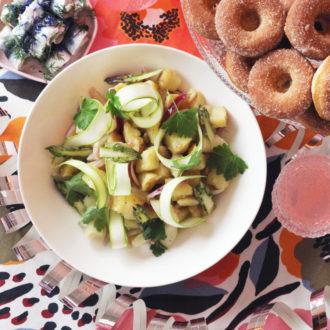Sur une table dressée sont disposés des verres remplis d'un breuvage rosé ainsi que plusieurs assiettes creuses contenant du poisson, de la salade de pommes de terre et des beignets.