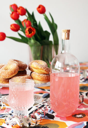 A bottle and a glass contain a pink beverage, while a platter of doughnuts and a vase of red tulips are visible in the background.