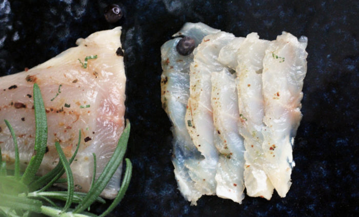 Thin slices of fish are arranged on a board.