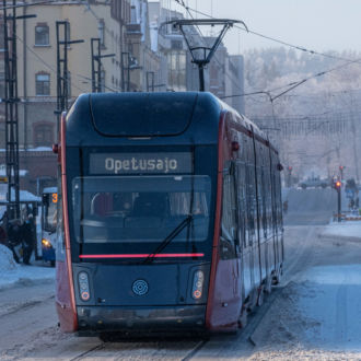 A tram goes down a snow-covered street.