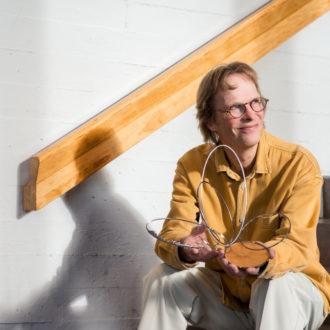 Un homme assis sur les marches d'un escalier tient entre ses mains une sculpture constituée d'anneaux métalliques et d'un socle en bois.