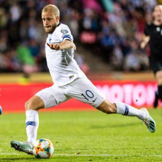 Um jogador de futebol finlandês está prestes a chutar a bola enquanto um jogador italiano corre em sua direção.