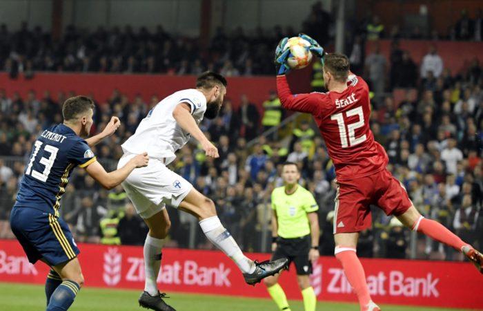 Ein Fußballspieler ist in die Luft gesprungen und der gegnerische Torwart hat den Ball in der Luft abgefangen.