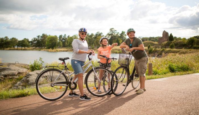 Uma mulher, uma criança e um homem estão de pé com suas bicicletas em uma estrada costal em um dia de verão.