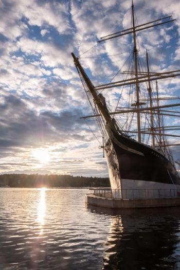 Um navio de madeira com diversos mastros está ancorado com a margem de um litoral ao fundo