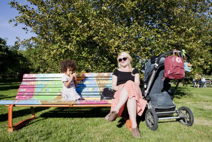 Una madre y su hija están sentadas al sol en un banco del parque.