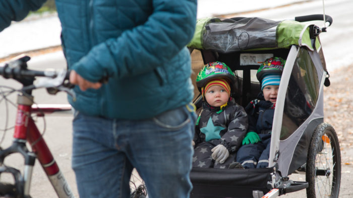 A man walks a bicycle that has a trailer with two toddlers sitting in it.