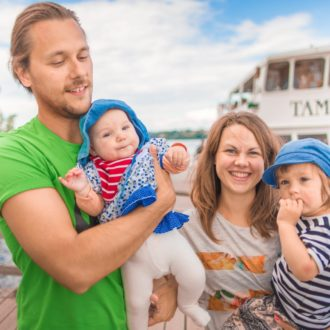 A man, a baby, a woman and a small child are on a ferry dock on a summer day.