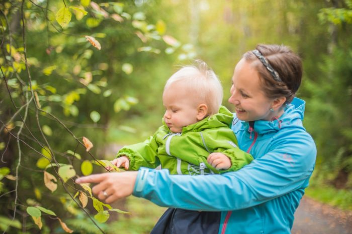 A woman and a baby are pointing at tree leaves beside a forest path.