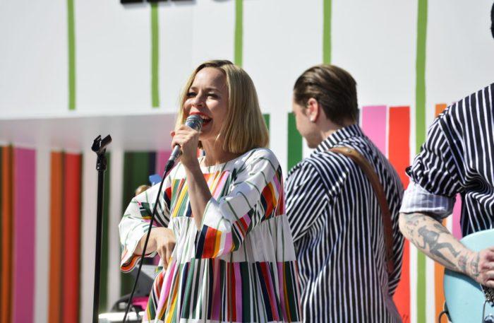 امرأة ترتدي قميصًا ملونًا تمسك بميكروفون وتغني.