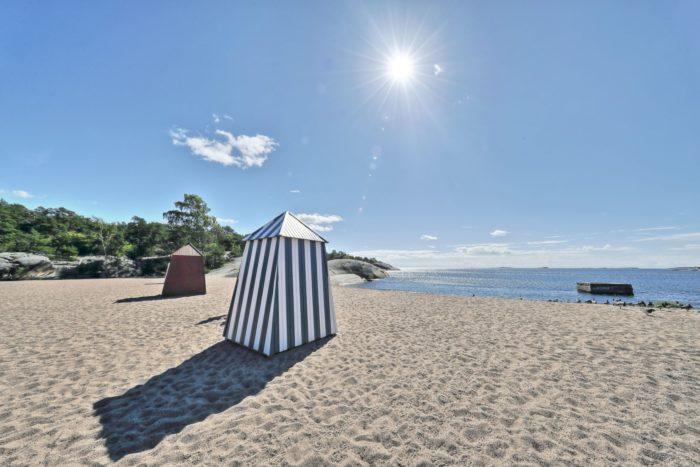 Várias cabanas de madeira pintadas com decoração estão localizadas em uma praia arenosa, sob um céu claro e ensolarado.