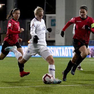 一名芬兰球员在踢球,阿尔巴尼亚球员从背后追赶她。