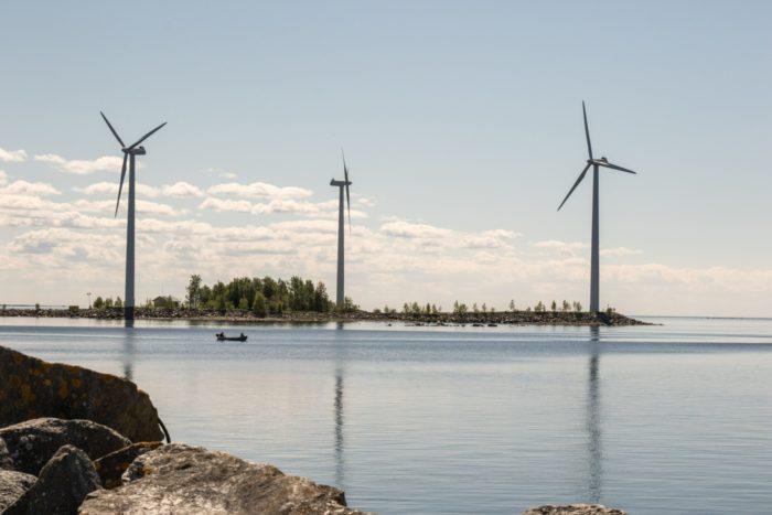 Trois éoliennes tournent aux abords d'un rivage.