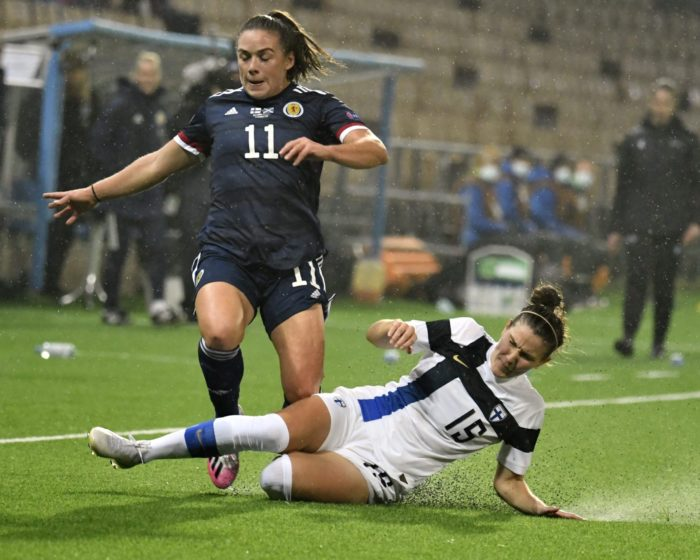 A Finnish player slide tackles a Scottish player.