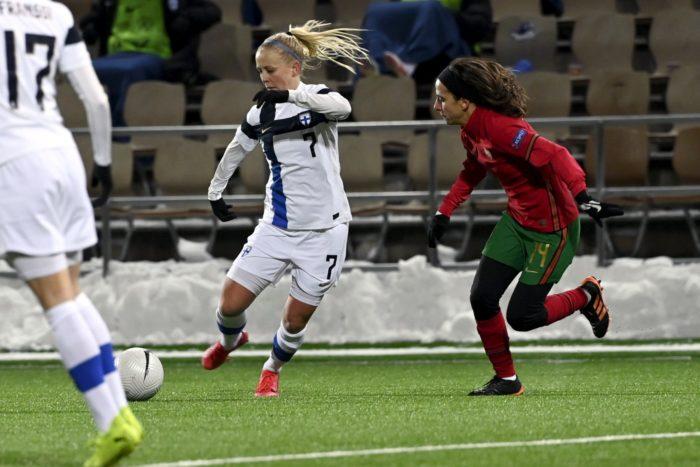A Finnish player kicks the ball as a Portuguese player runs after her.