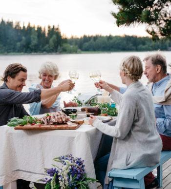رجلان وامرأتان يجلسون على طاولة على ضفة بحيرة ويرفعون كؤوسهم نخبًا.