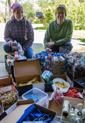 Duas mulheres se ajoelham atrás de um grupo de caixas e recipientes cheios de pedaços de lixo plástico.