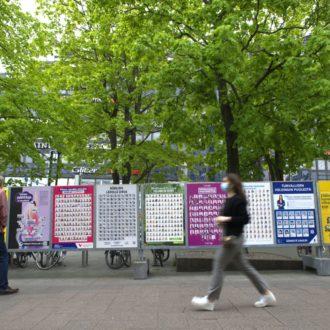 In einem von Bäumen gesäumten Park gehen Fußgänger an einer Reihe von Wahlplakaten vorbei.