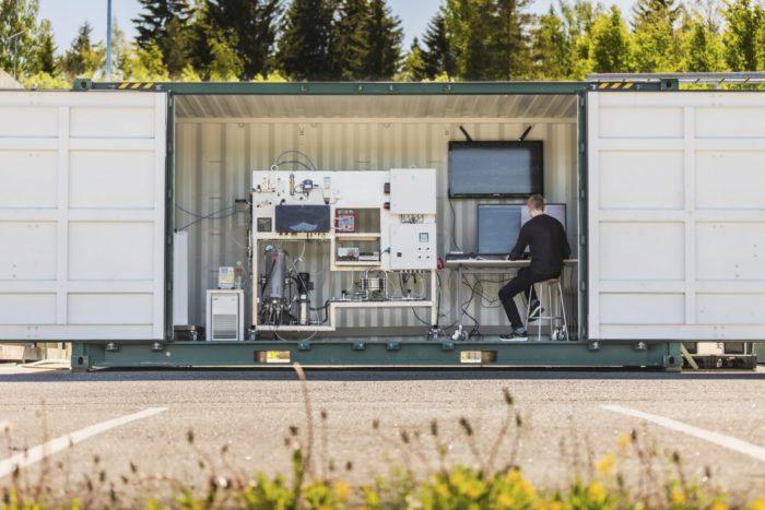 Un homme est assis face à des ordinateurs et à une machine disposés dans un conteneur d'expédition métallique ouvert.