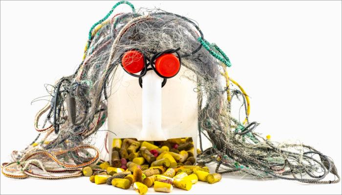 Um rosto feito de lixo plástico tem cabelos grisalhos, olhos vermelhos e uma boca que está vomitando uma pilha de protetores de ouvido de espuma.