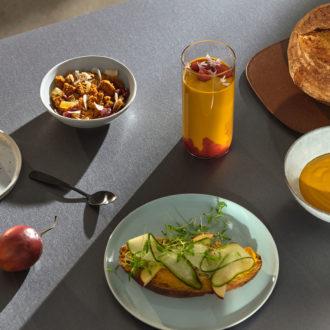 Des assiettes et bols contenant de la soupe, du pain et d'autres produits alimentaires sont disposés sur une table.