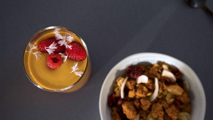Un verre contient un liquide et des petits fruits rouges.