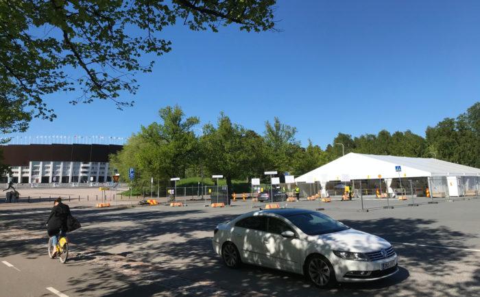 يتحرك سائق دراجة وتتحرك سيارة عبر مأوى يشبه الخيمة في ساحة انتظار السيارات في الإستاد.