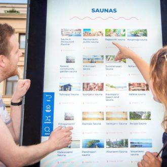 Женщина и мужчина указывают на изображение на большом наружном экране.