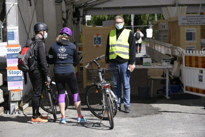 امرأتان تقفان بجانب دراجتَيهما أمام مكتب وتتحدثان مع رجل يرتدي صديريًّا عاكسًا للضوء.