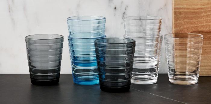 Sete copos estão dispostos em uma mesa.