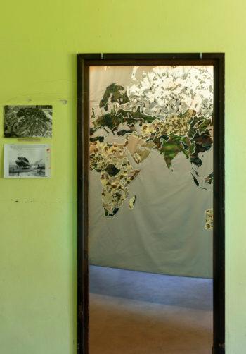 Eine aus Stoffstücken gefertigte, eingerahmte Landkarte hängt an der Wand.