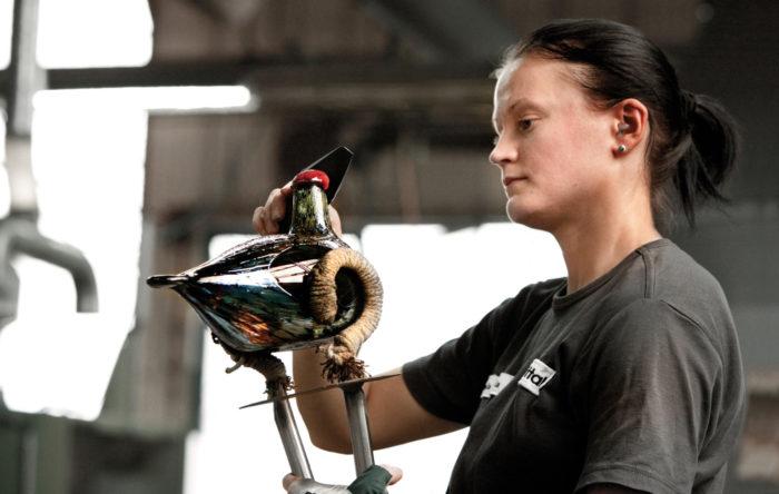 Uma mulher está polindo um pássaro de vidro.