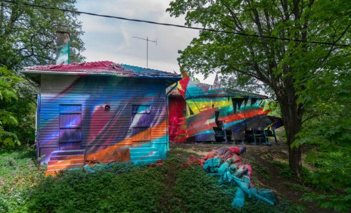 Bunte Farbflecken überziehen ein kleines Holzgebäude.