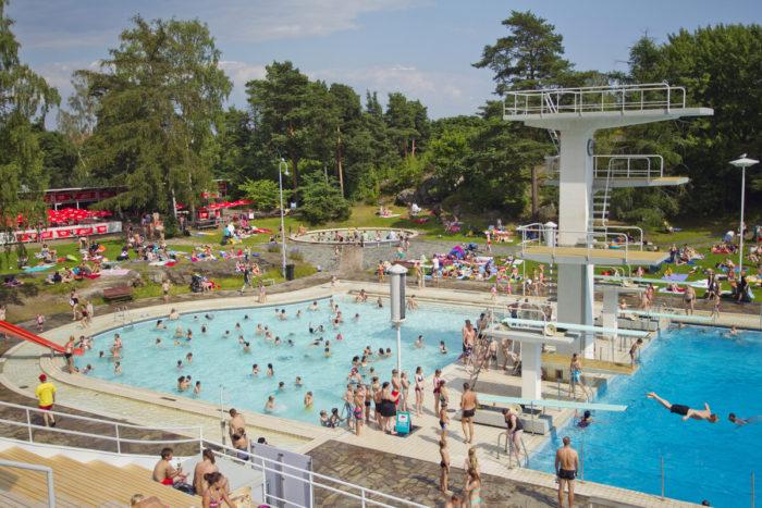 Uma piscina externa com área de mergulho e área infantil, com árvores ao fundo.