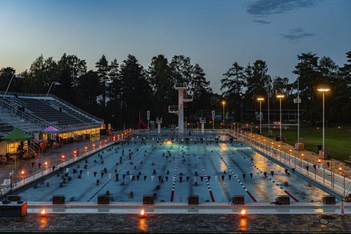 Uma piscina ao ar livre iluminada por velas e luzes ao entardecer, com árvores ao fundo.