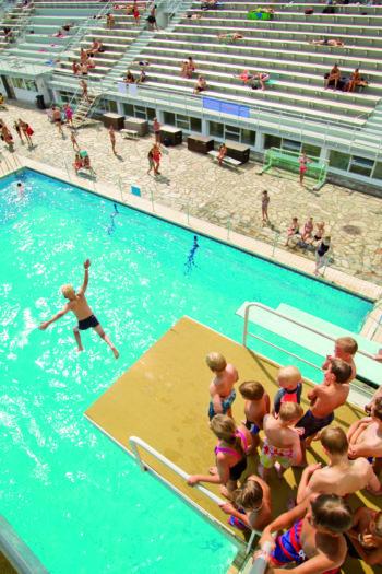 Crianças aguardam sua vez na plataforma de mergulho de 10 metros enquanto uma delas pula na piscina.