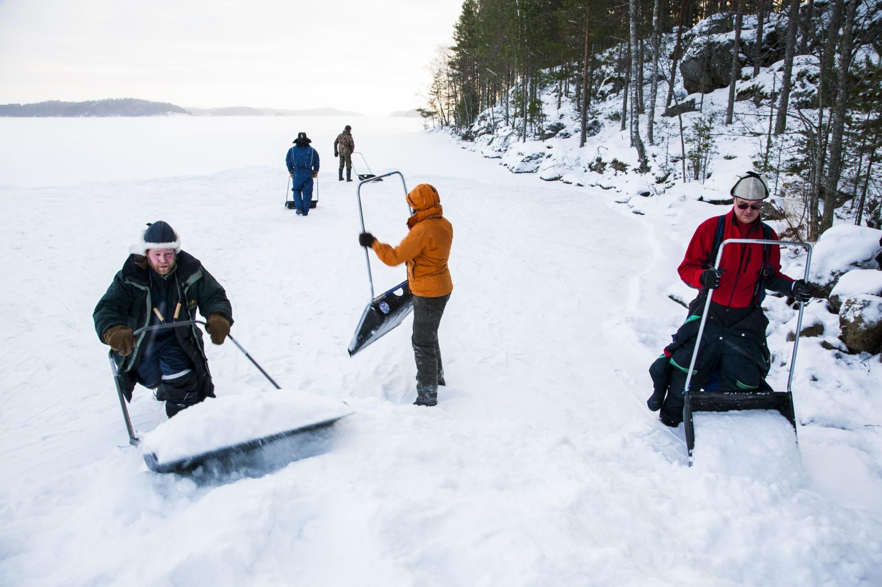 Au bord d'un lac à la surface recouverte de glace, des gens s'aident de pelles pour constituer des amas de neige.