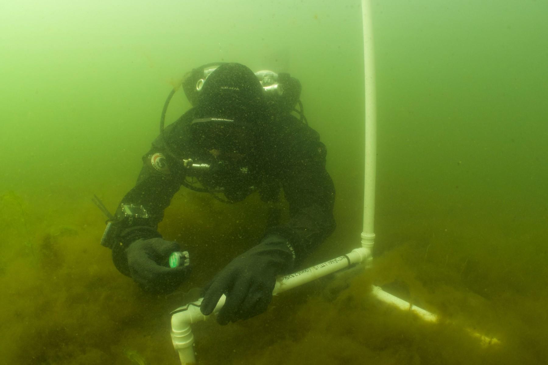 Un plongeur manipule des appareillages sur un fond marin.