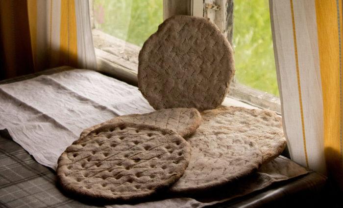 Несколько плоских хлебных коржей лежат на столе перед окном.