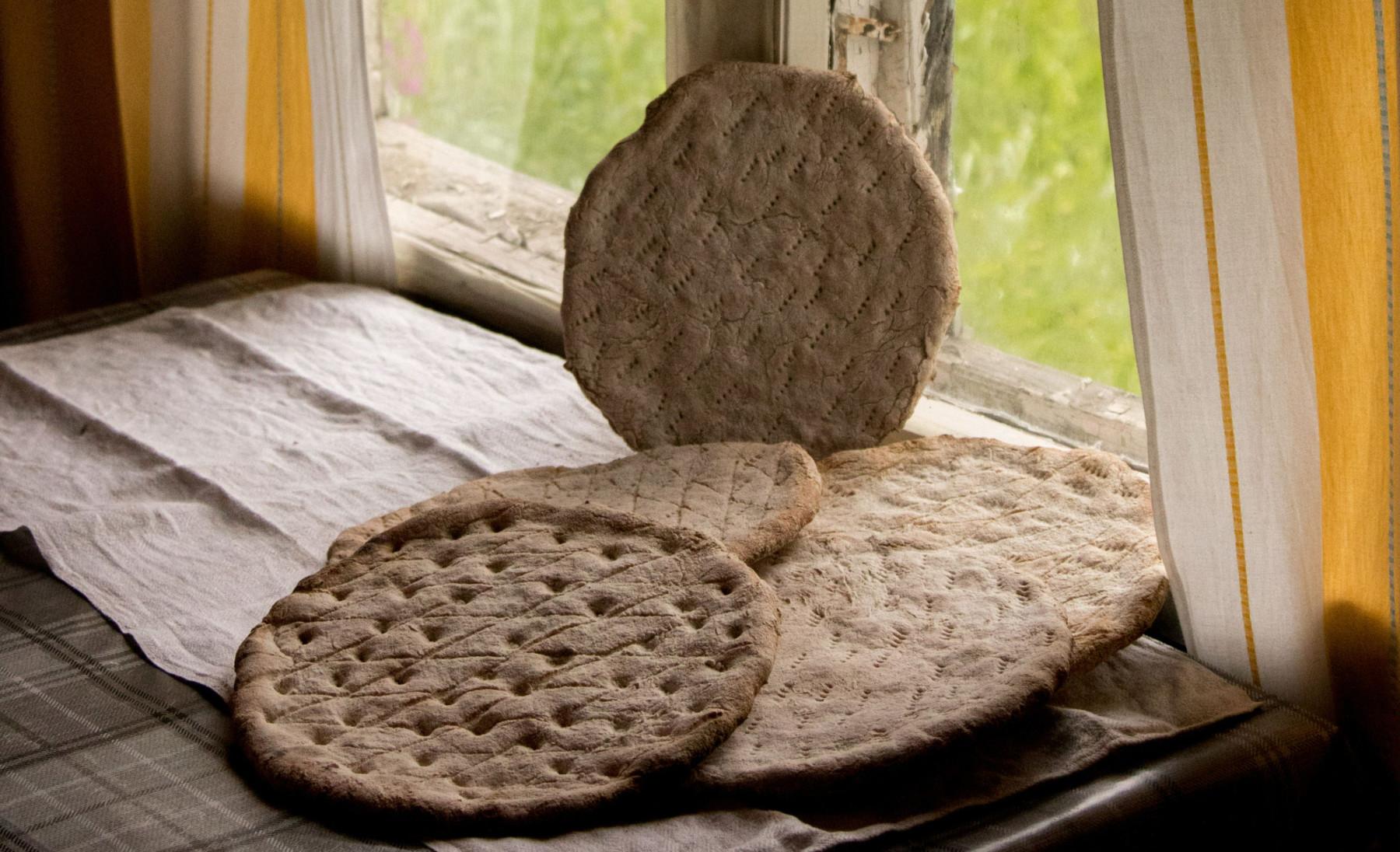 Mehrere runde, flache Brotstücke sind auf einem Tisch vor einem Fenster angeordnet.