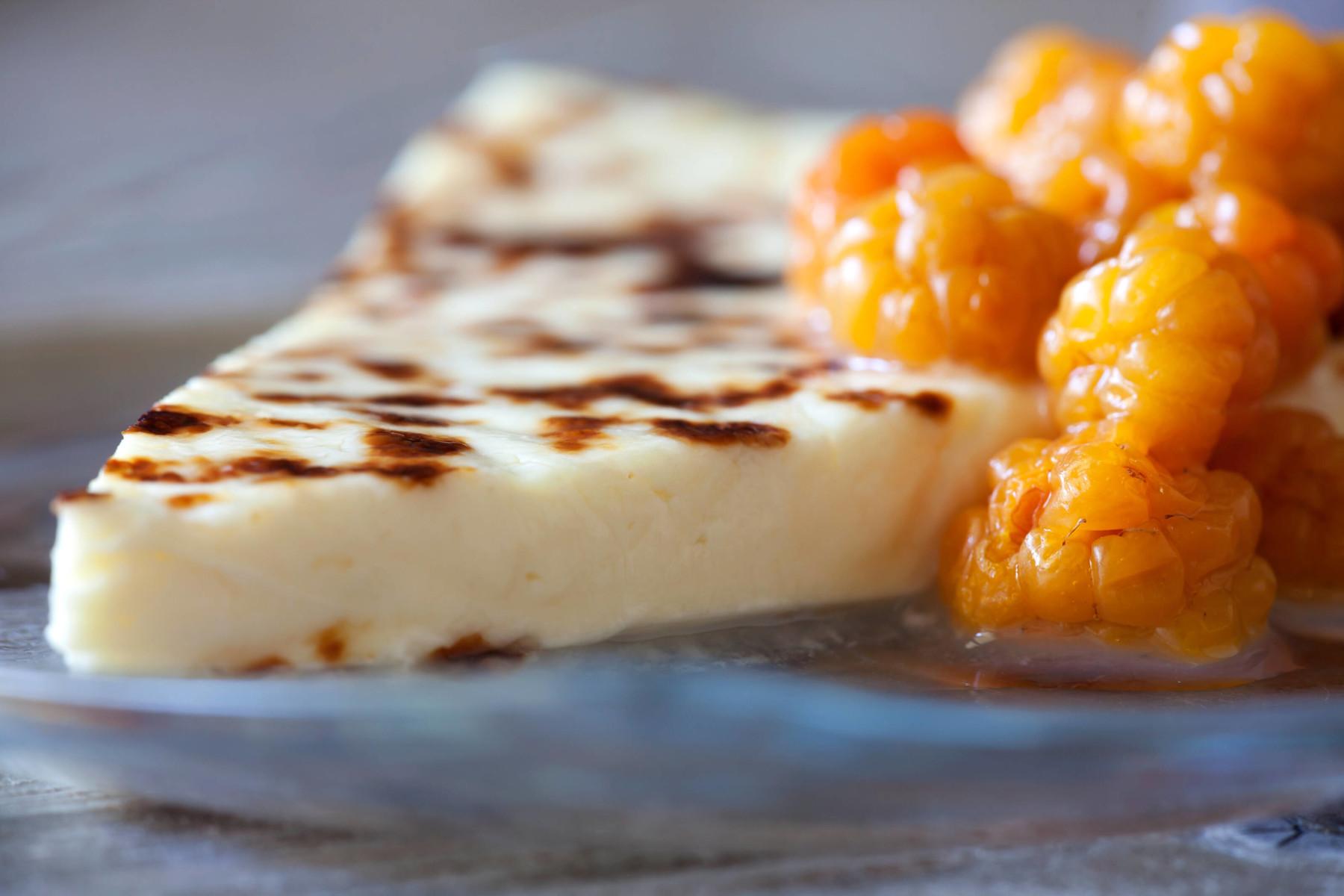 Ein Stück Käse und große orangefarbene Beeren auf einem Teller.