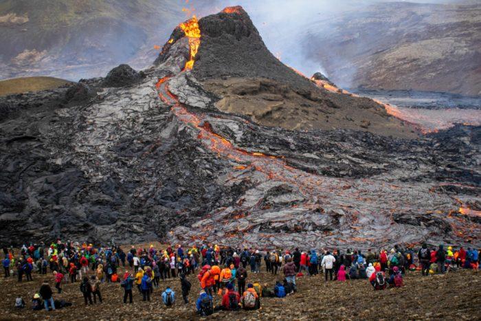 Поток лавы течет с горы, и группа людей стоит, наблюдая его с расстояния.