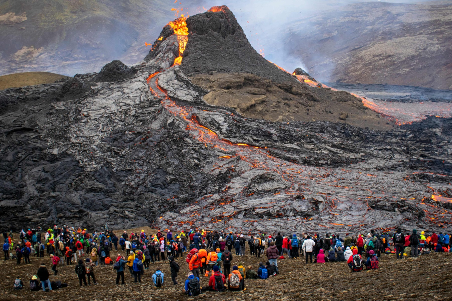 A stream of lava flows down a mountain while a group of people stand and watch from a distance.