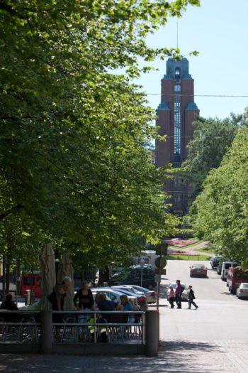 В конце усаженной деревьями улицы виднеется башня.