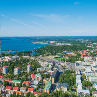 Una vista aérea de los edificios de una ciudad, con un lago al fondo.